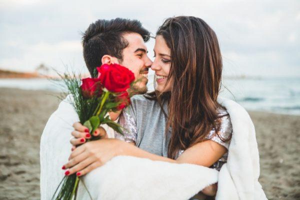 Любить пара, сидя на пляже с букетом роз | Бесплатно Фото