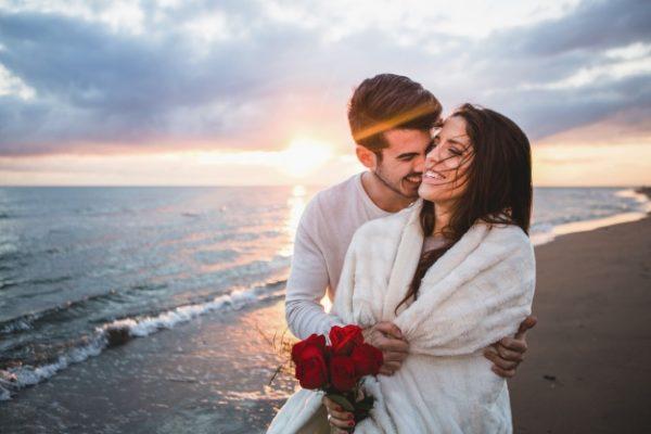 Улыбаясь пара идет на пляже с букетом роз на закате | Бесплатно Фото
